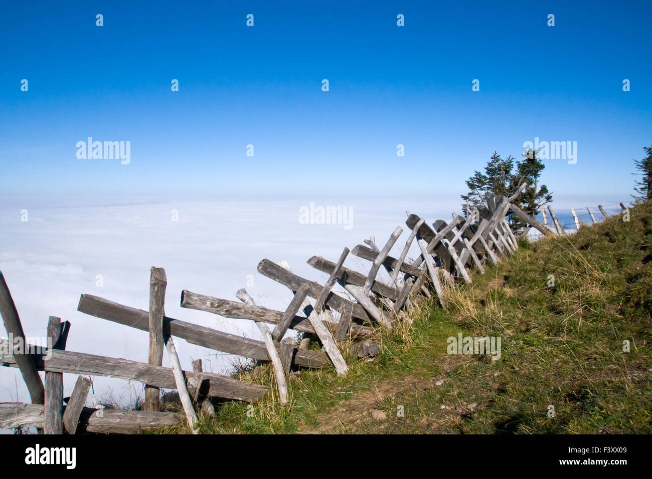 A wooden fence above the clouds in the swiss alps - Stock Image