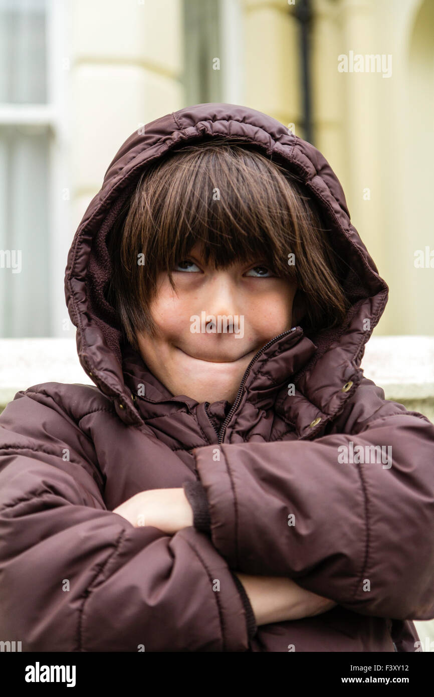 Ten year old caucasian boy standing outside, cold, arms folded, waiting, making comical face - Stock Image