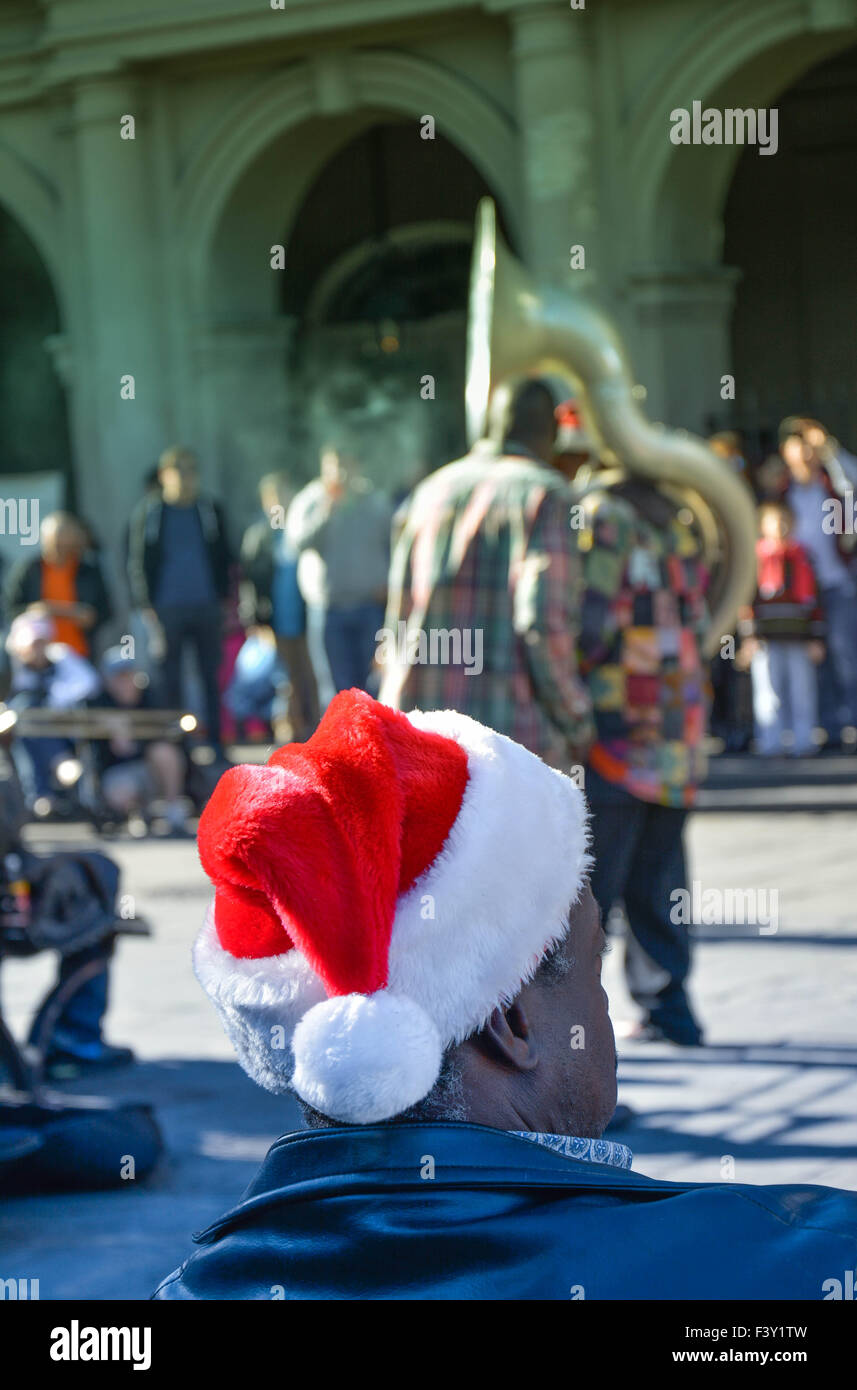 Rear view of man wearing Santa hat enjoying entertainment by street musicians, Jackson Square, French Quarter, New Orleans, LA Stock Photo
