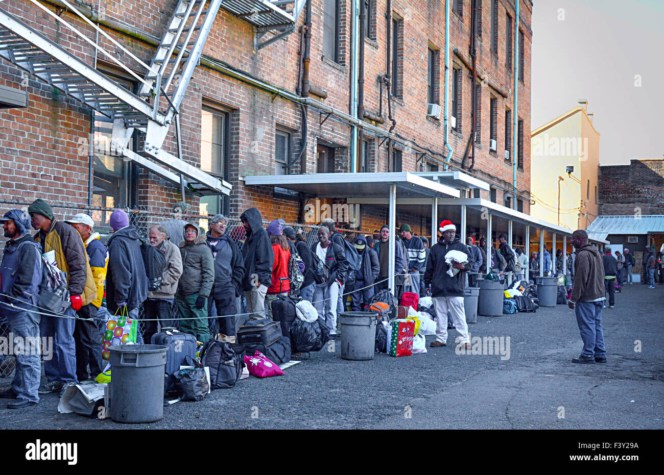 People of all races and ages stand in line waiting their turn for food and clothing donations at charity mission - Stock Image