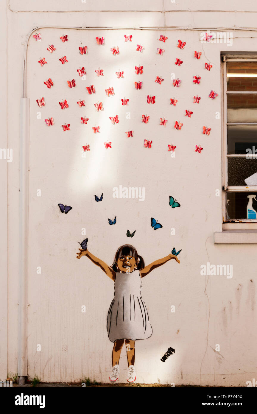 Recycle Girl graffiti by Unify in Whitstable contains butterflies made from Coca-Cola cans. - Stock Image