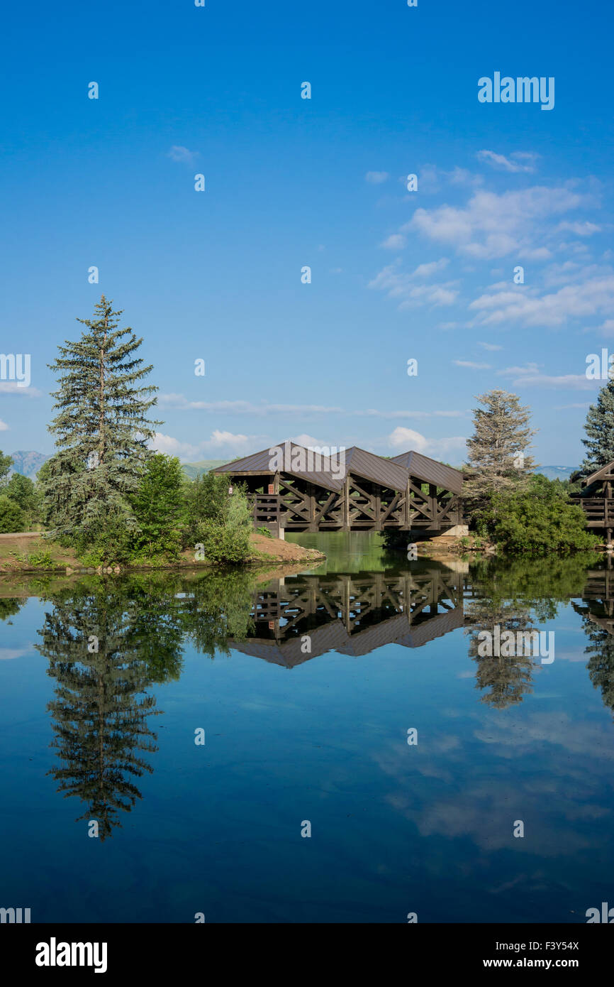 A wooden foot bridge over a pond in a park in Lakewood Colorado - Stock Image