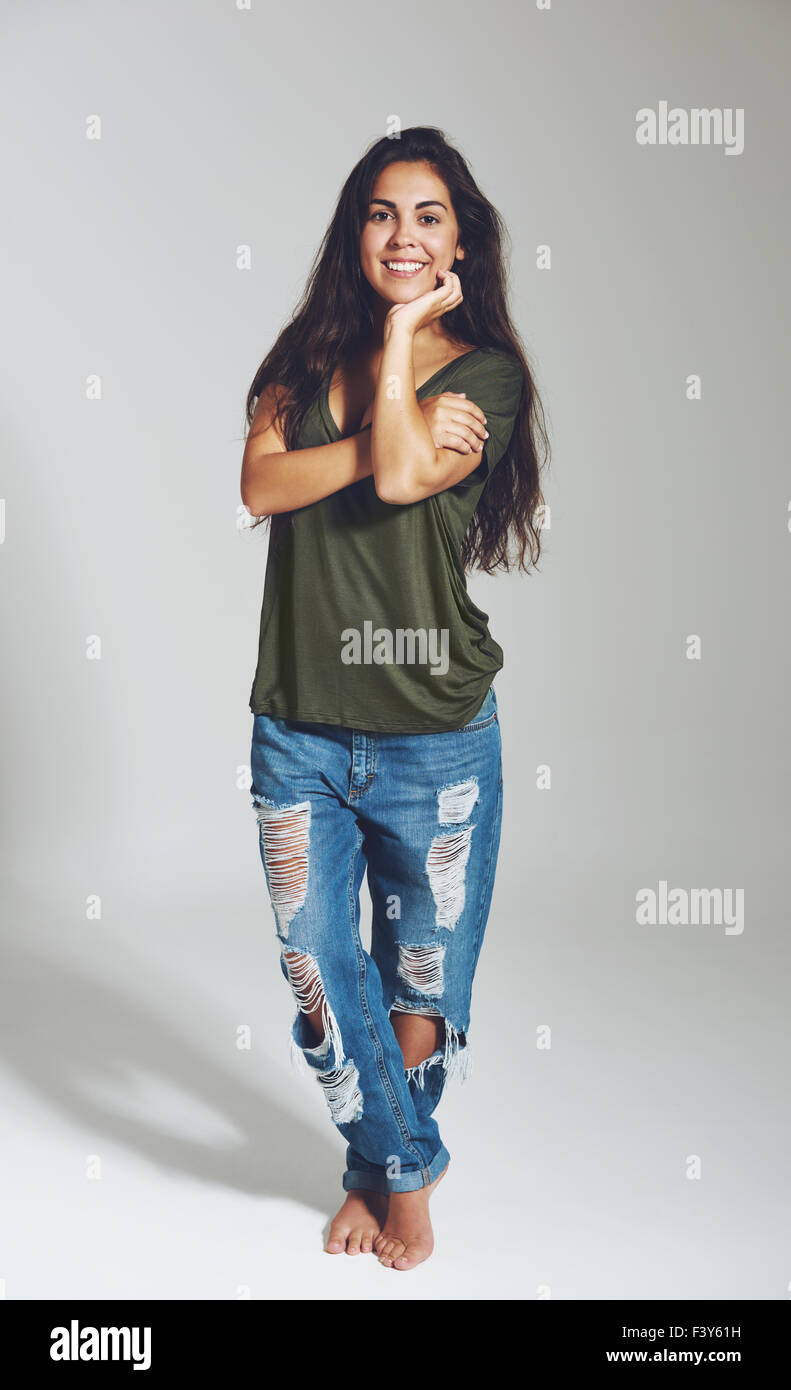 Trendy young student in designer jeans standing cross legged and barefoot smiling happily at the camera - Stock Image