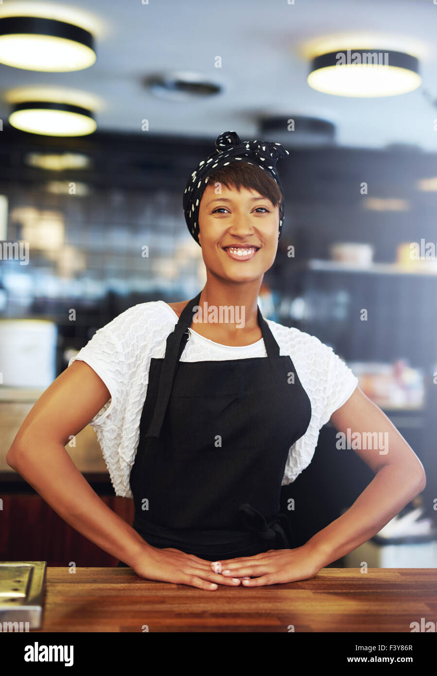 Confident successful young small business owner standing behind the counter in her coffee shop giving the camera - Stock Image