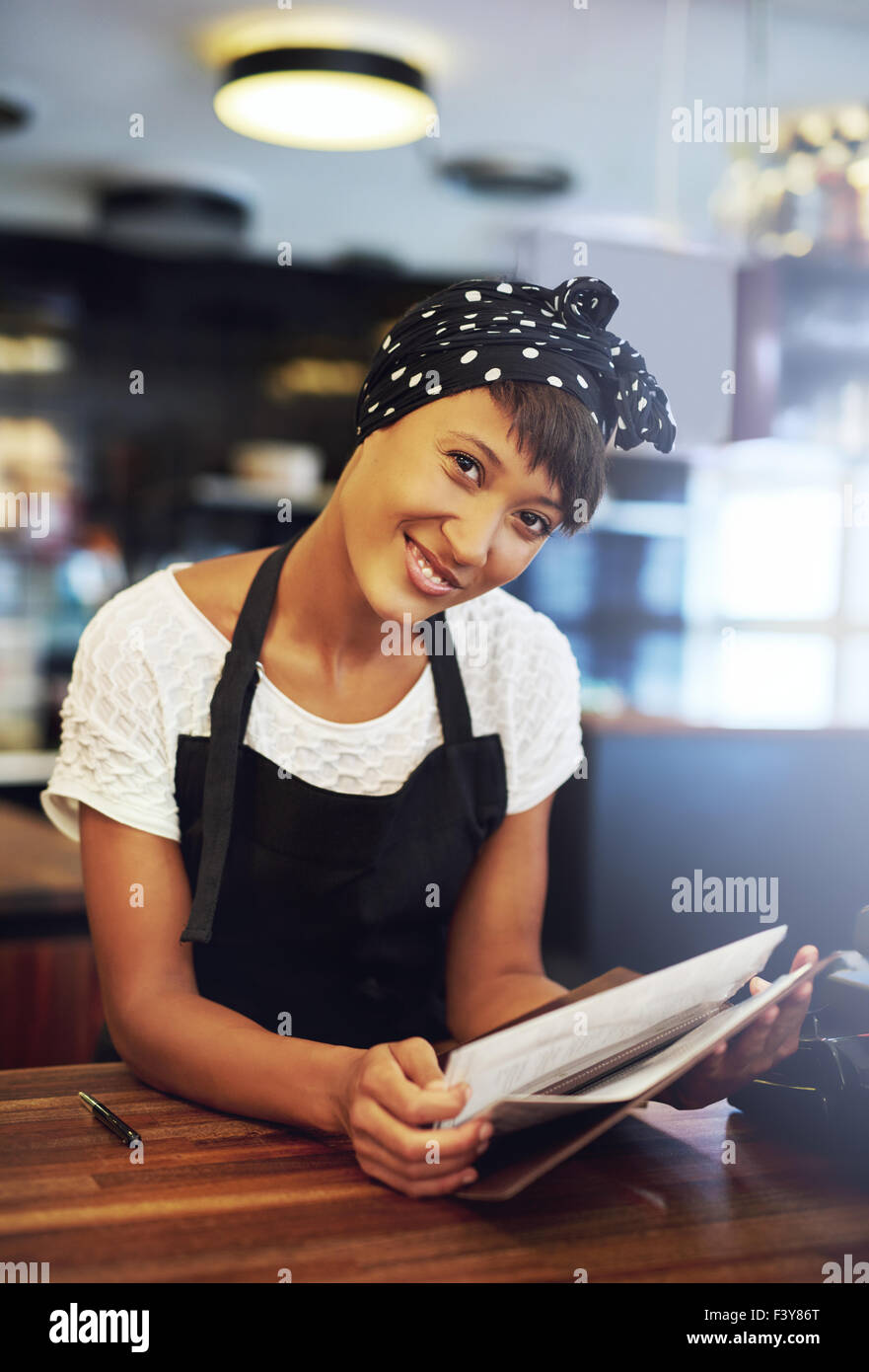 Smiling young coffee house owner standing behind the counter in an apron leaning forwards to offer the menu with - Stock Image