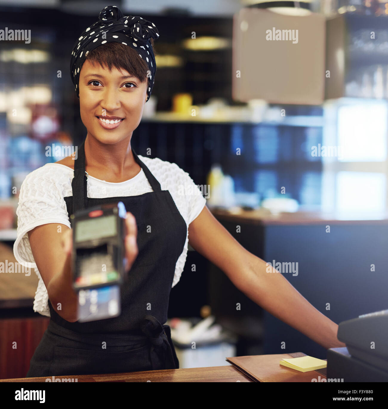 Young shop owner requesting payment holding out a handheld banking machine for a customer to enter the code for - Stock Image