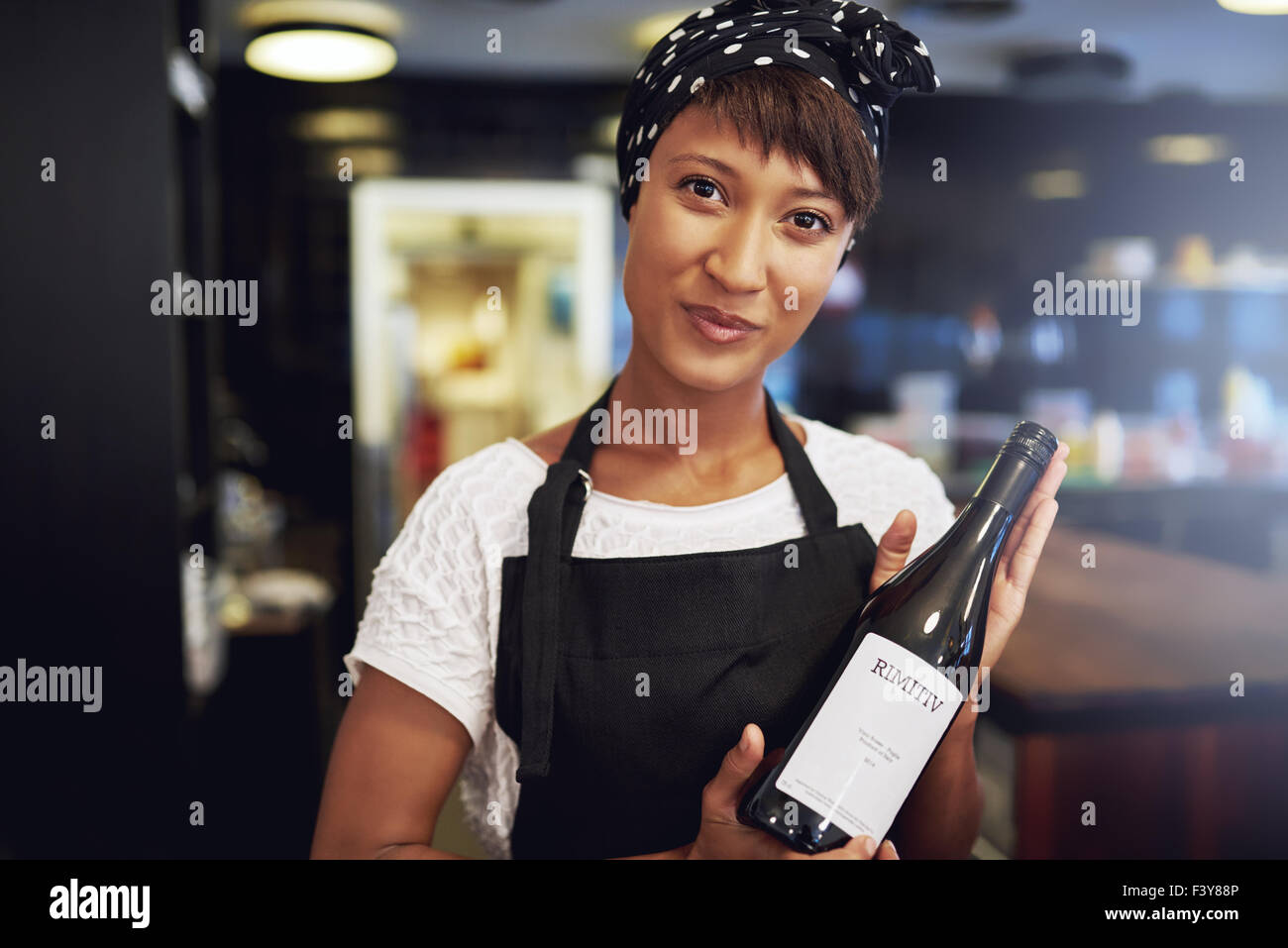 Attractive young African American lady in an apron presenting a bottle of red wine to a customer in a restaurant - Stock Image