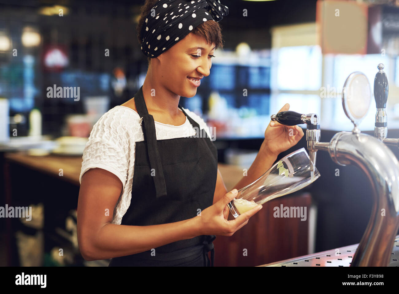 Young attractive female African American bartender pouring a glass of draft beer from the keg dispensing it from - Stock Image