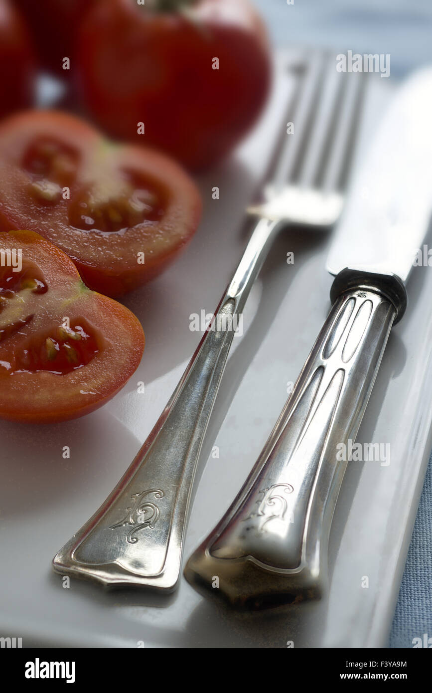 Old silver cutlery (Jugendstil) and Tomatoes Stock Photo