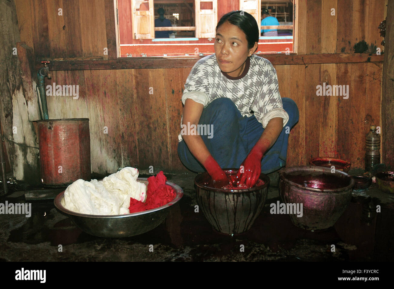 Young burmese woman dyeing clothes at Inle Lake, Shan State, Myanmar - Stock Image