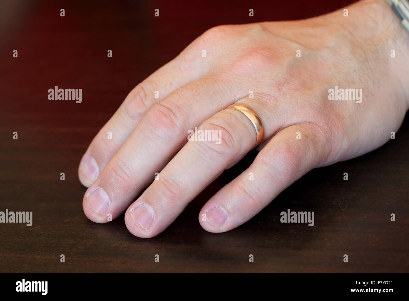 Adult male left hand on a wooden table - Stock Image
