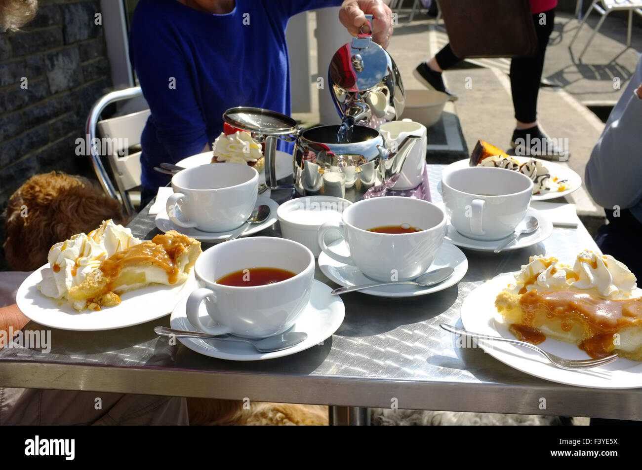 A table full of cups of tea and plates of cake for afternoon tea at a seaside cafe serving afternoon tea in Wales. & A table full of cups of tea and plates of cake for afternoon tea at ...