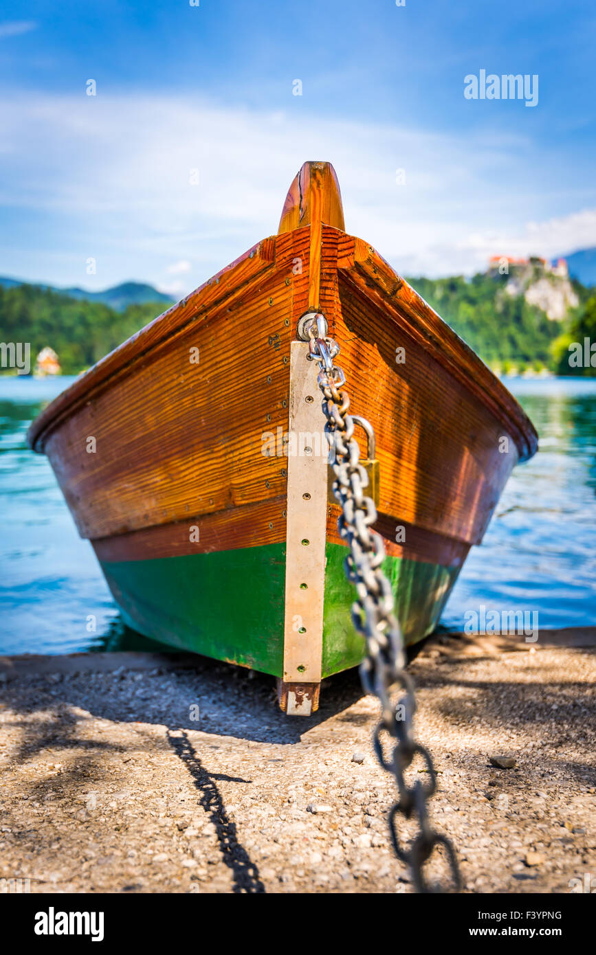 Detail of Anchored Wooden Tourist Boat on Shore of Bled Lake, Slovenia with Bled Castle in Background - Stock Image