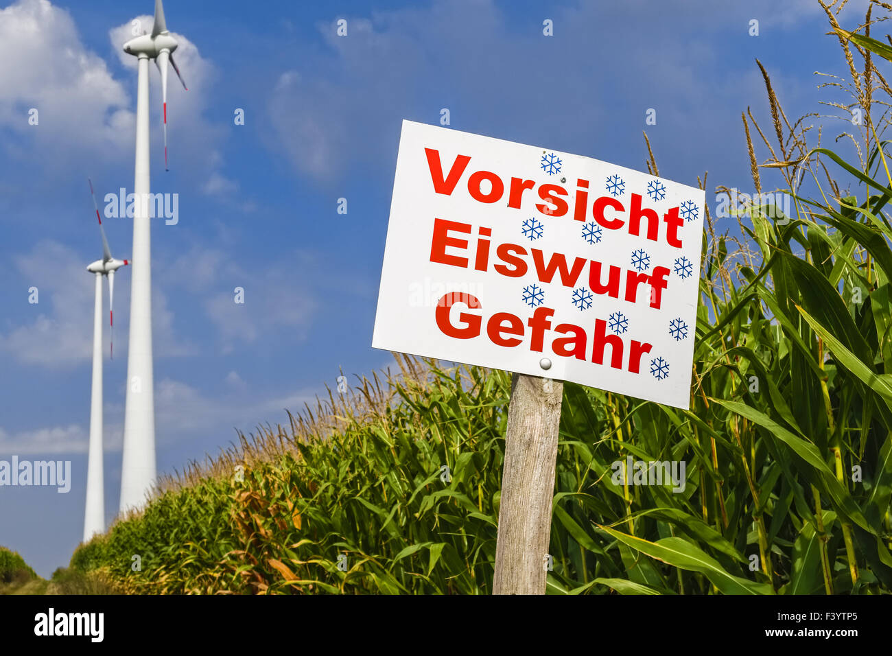 Danger sign in front of wind turbines - Stock Image