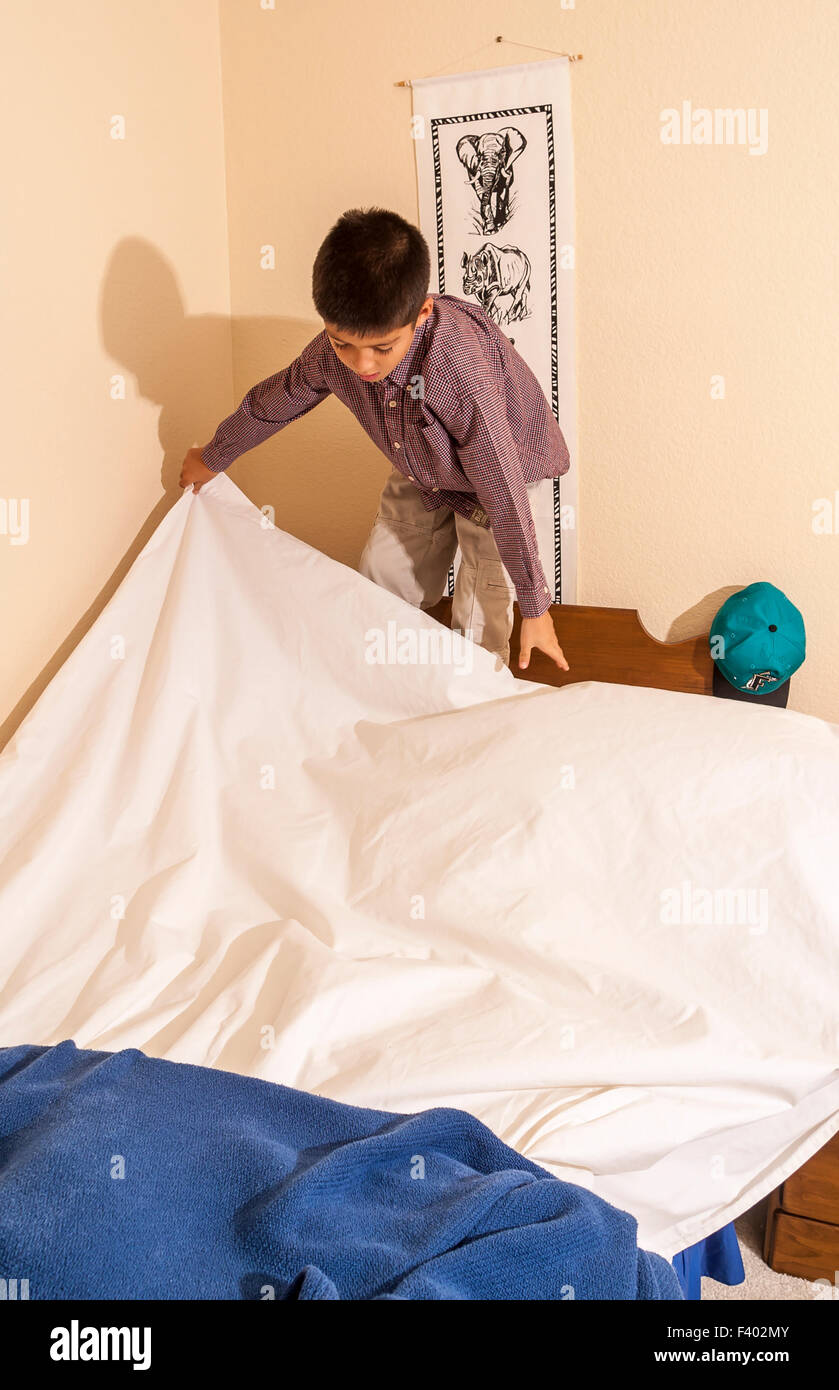Young Korean/American boy 8-10 year olds years old  making his bed.   MR ©Myrleen Pearson - Stock Image