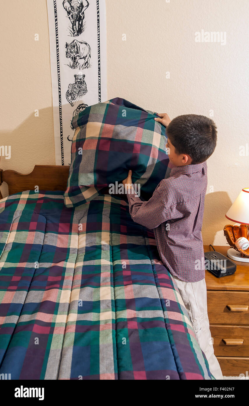 children making bed tidy tidying bedroom multi inter racial diversity racially diverse multicultural cultural interracial - Stock Image