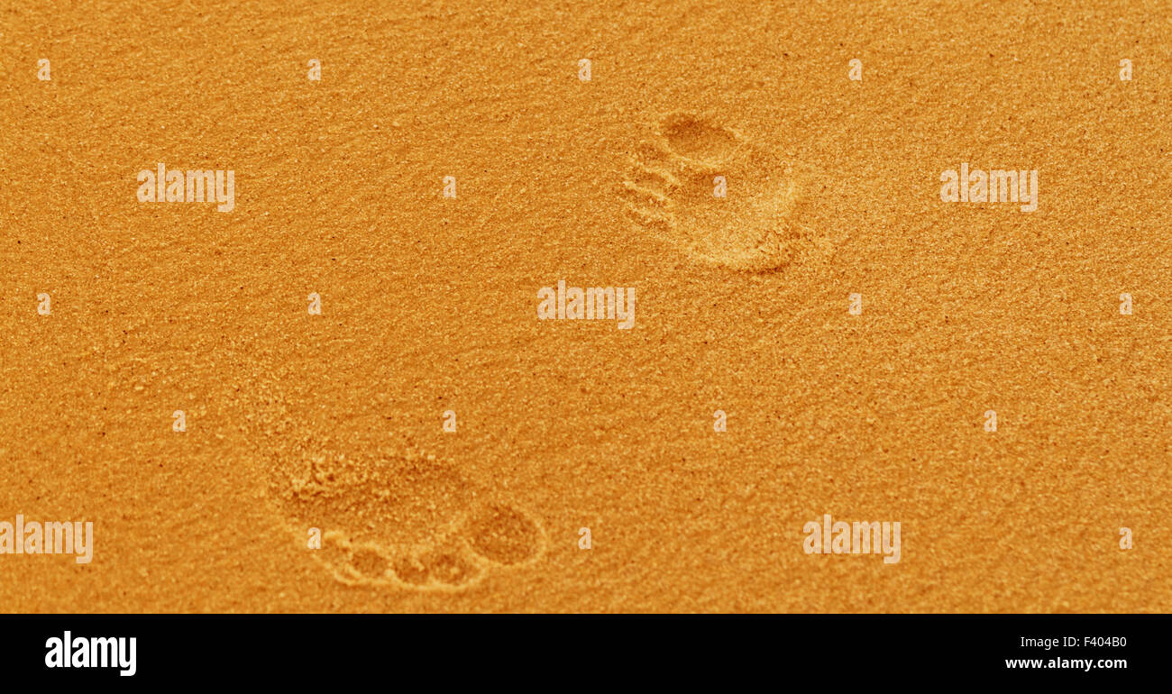 Photo of footprints in the coastal sand - Stock Image