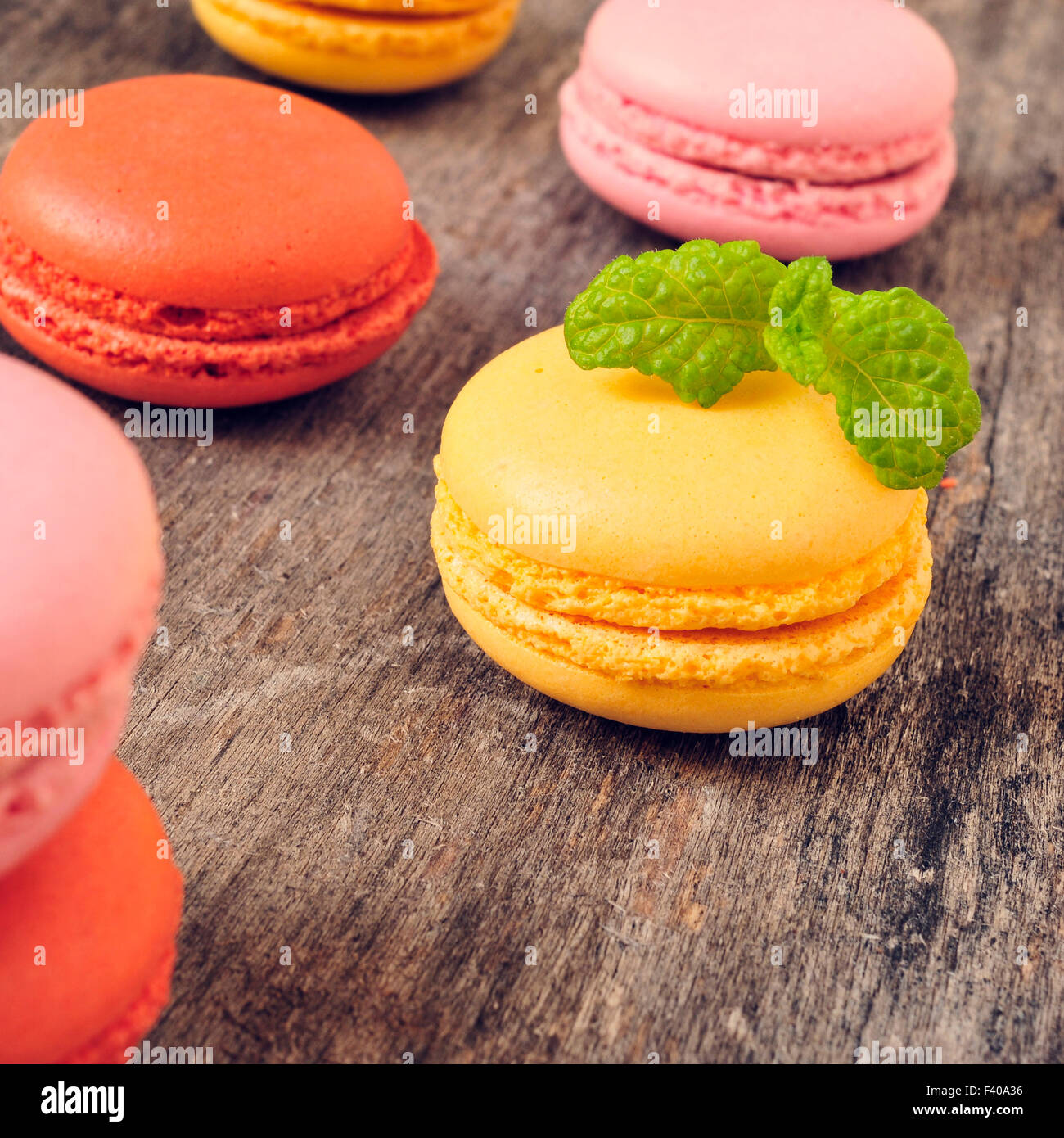 some appetizing macarons with different colors and flavors on a rustic wooden table - Stock Image