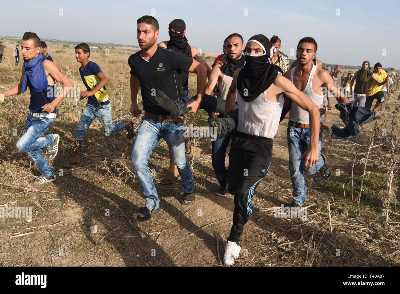 Gaza, Palestine. 13th Oct, 2015. A wounded Palestinian protester is evacuated after he was shot by Israeli troops - Stock Image