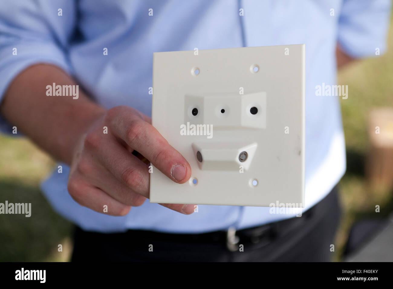 Man holding hidden camera with built in motion detector - USA - Stock Image