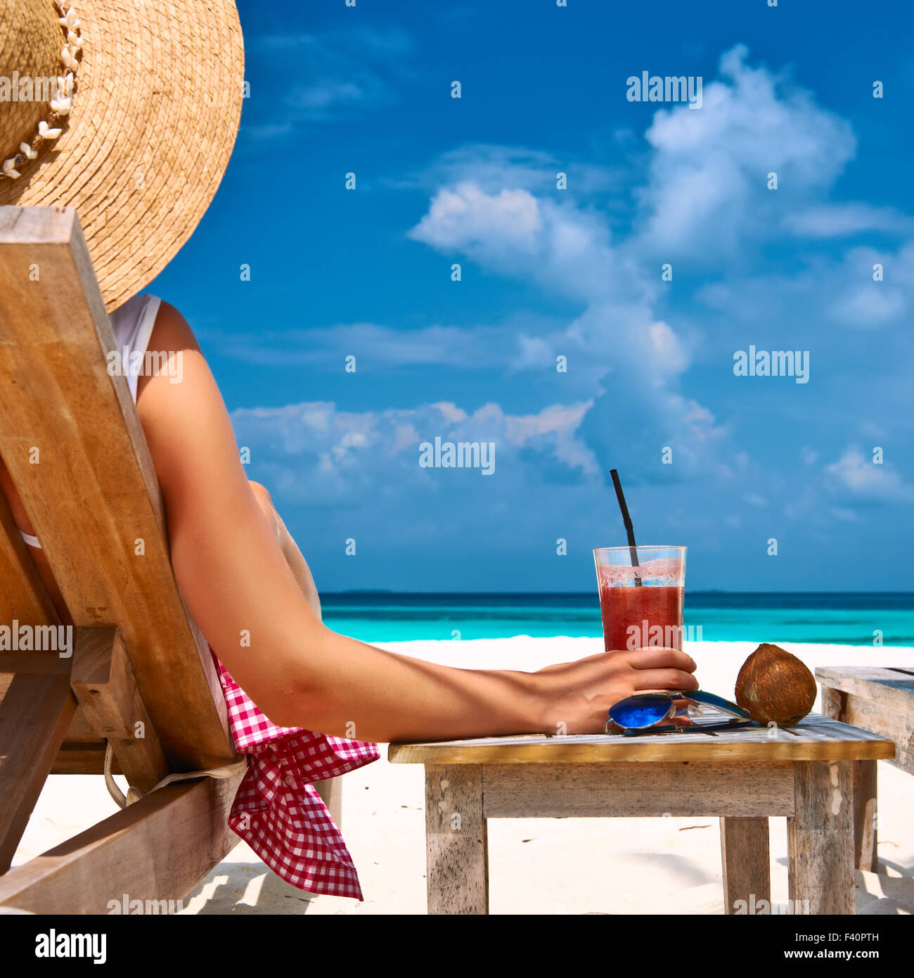 Woman at beach with chaise-lounges - Stock Image