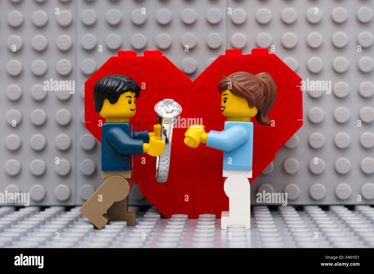 Lego man with ring makes marriage proposal to his girl standing in front of the heart on gray Lego baseplates. - Stock Image