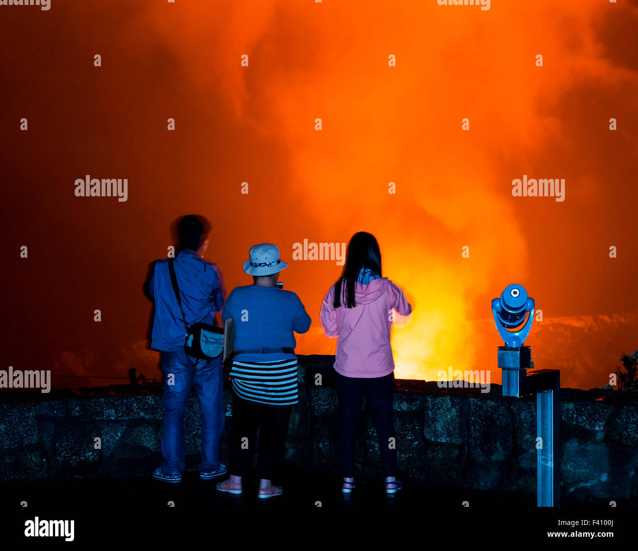 Visitors in silhouette at dusk, lava glowing Kilaueea Caldera volcano, Hawai'i Volcanoes National Park, Big - Stock Image