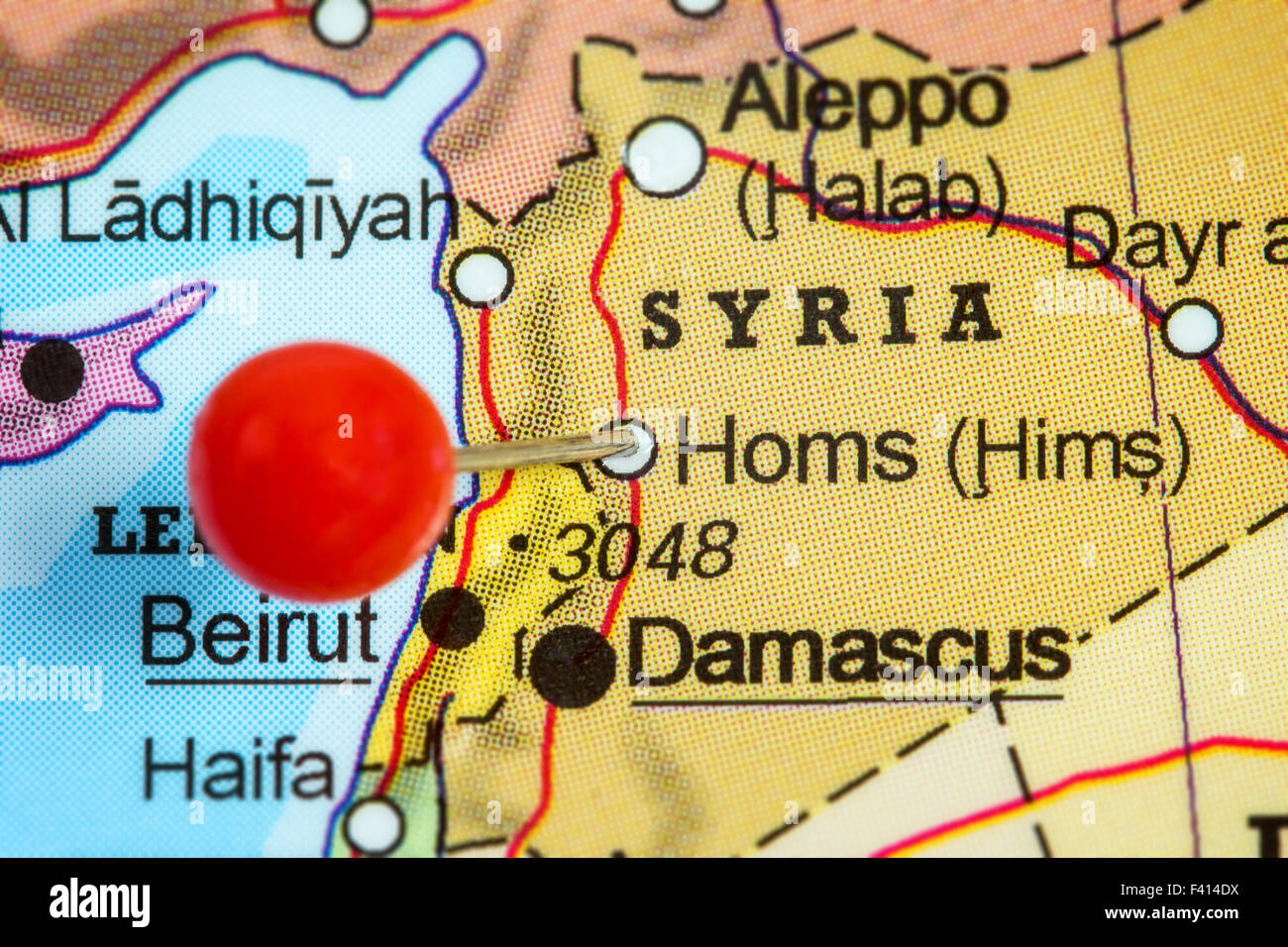 Close-up of a red pushpin in a map of Homs, Syria. - Stock Image