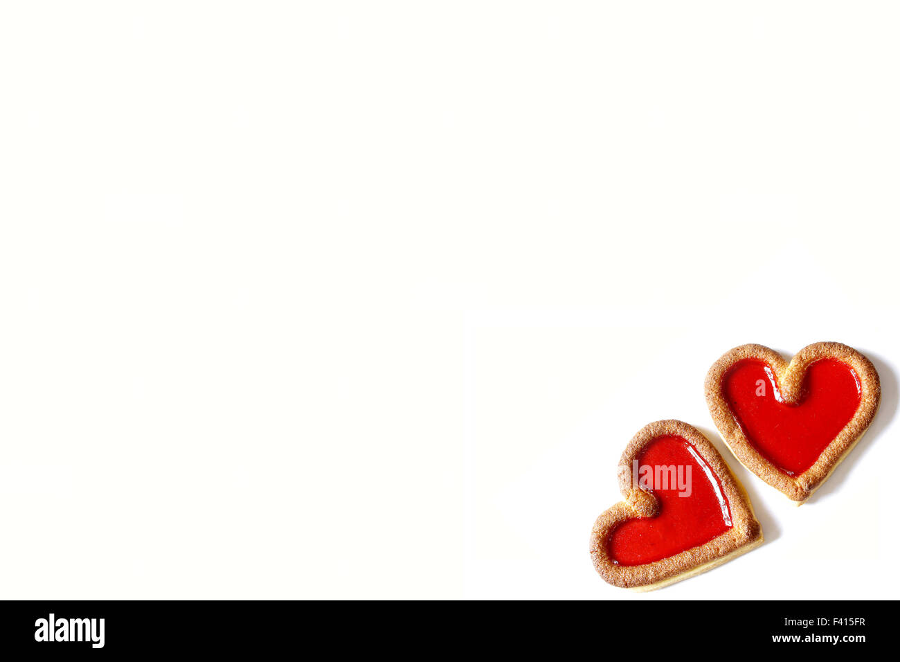 two red biscuit  hearts beating together on white background - Stock Image