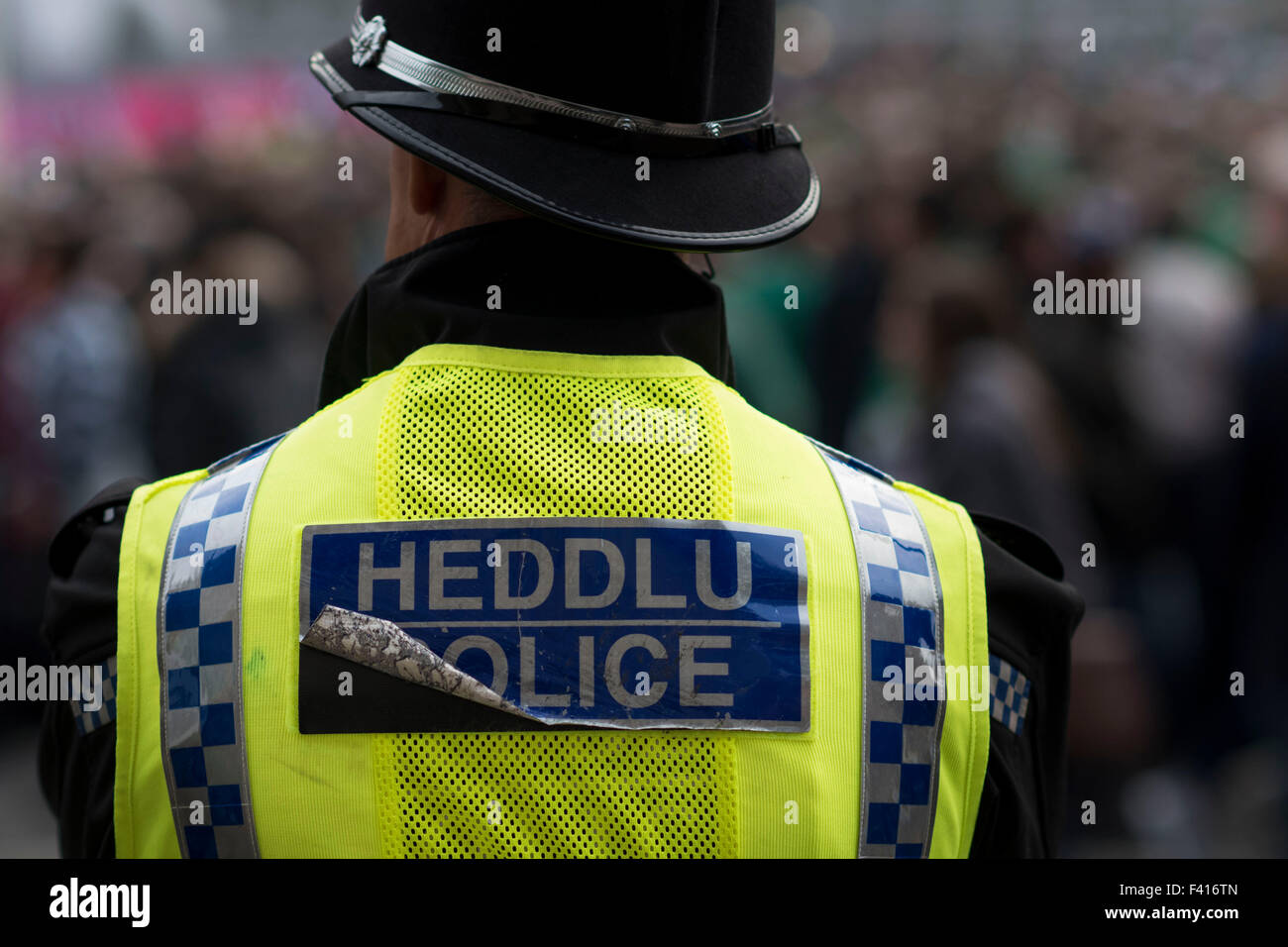 A Welsh police officer looks on at an event. The police force in Wales have suffered cutbacks in recent years. - Stock Image