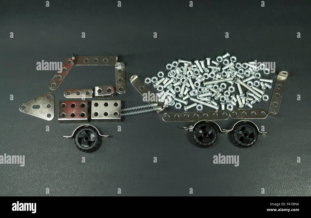Perforated metallic plates arranged in such a way as to resemble a loading truck filled with nuts and bolts - Stock Image