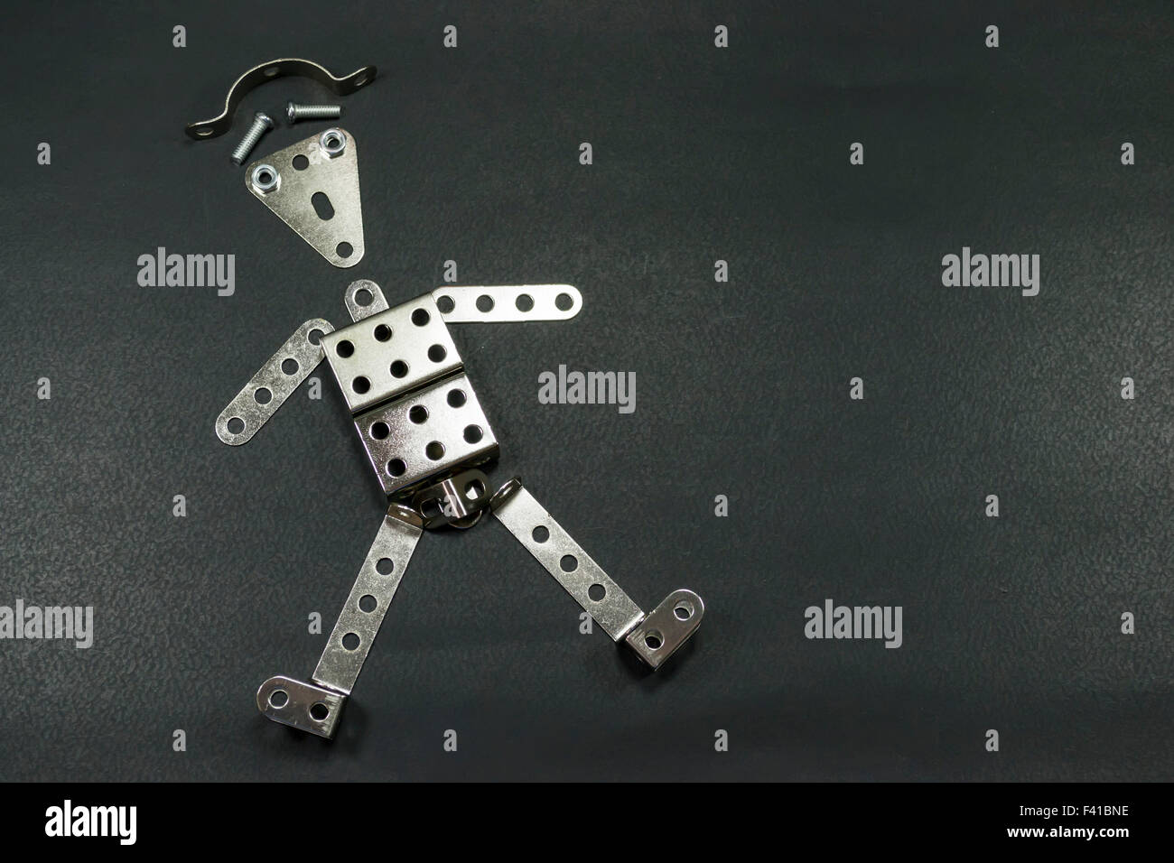 Perforated metallic plates arranged in the form of a funny robot or tin man , against a black background - Stock Image