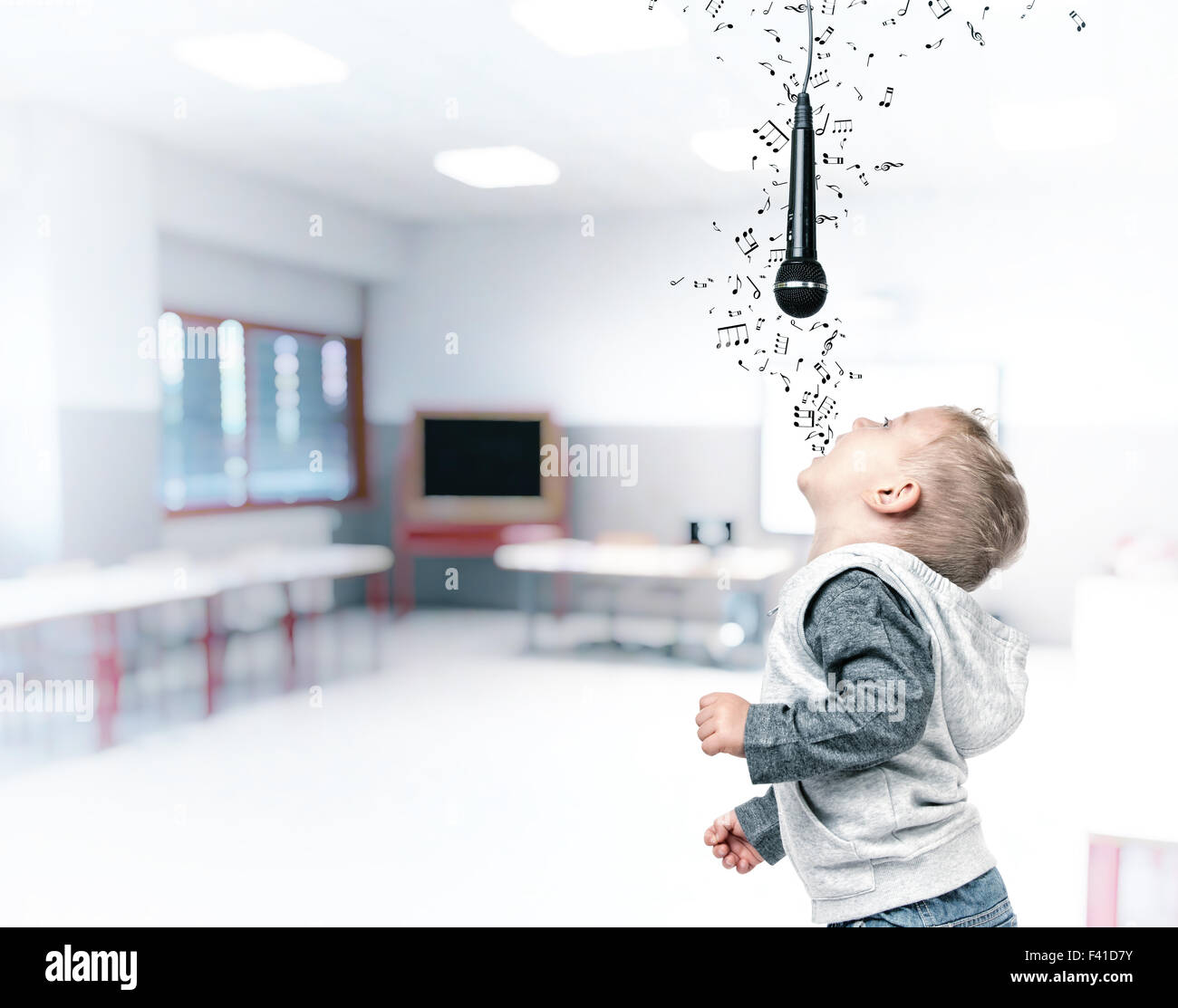 child sing and enjoy with microphonein class - Stock Image