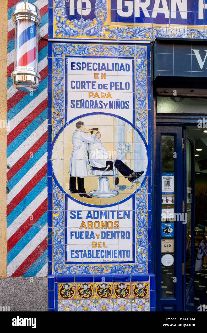 Painted Wall Tiles on Outside of Barbers Shop In Madrid - Stock Image