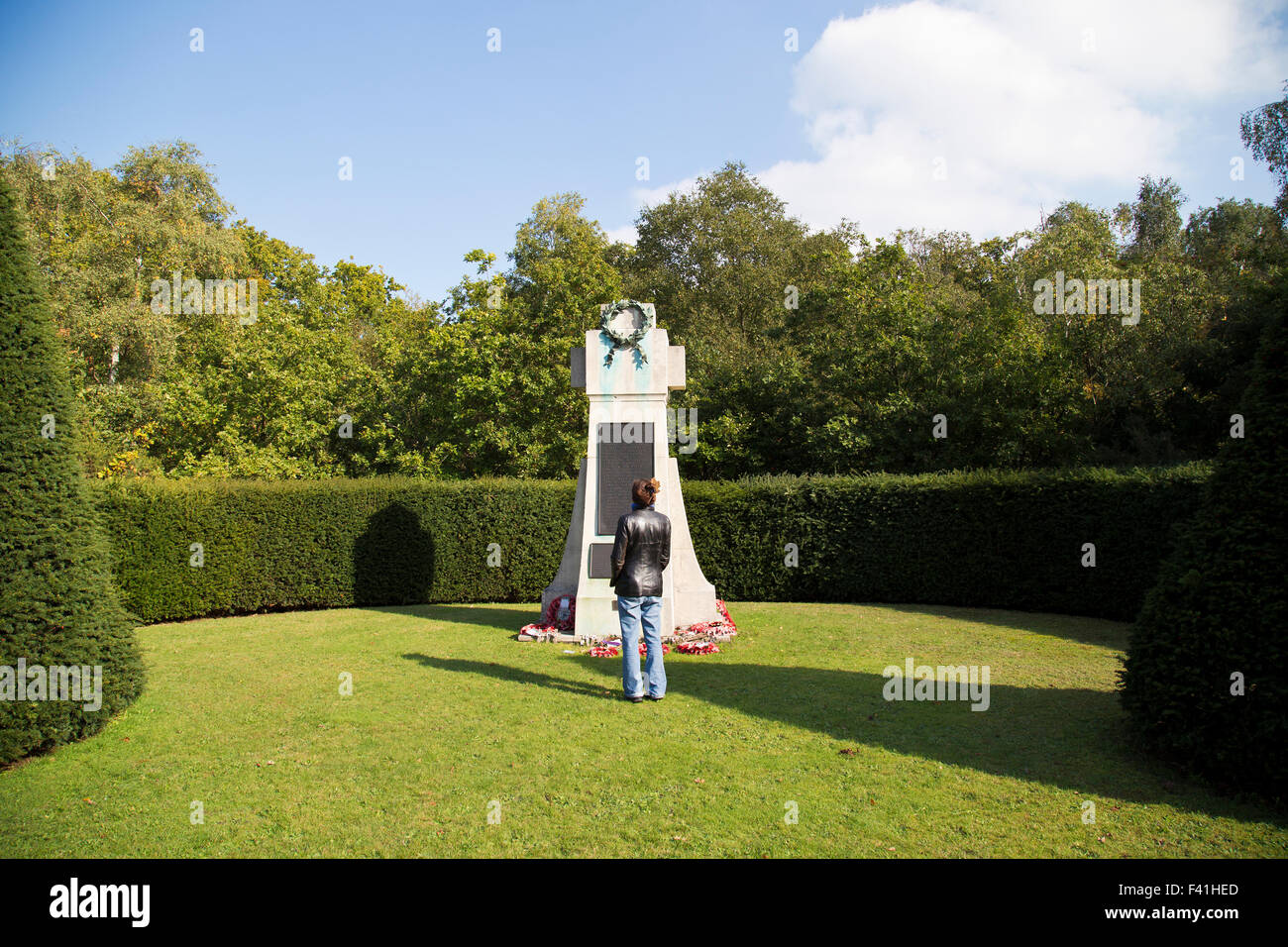 woman stands in front of the war memorial in the village of Keston in Bromley Kent UK - Stock Image