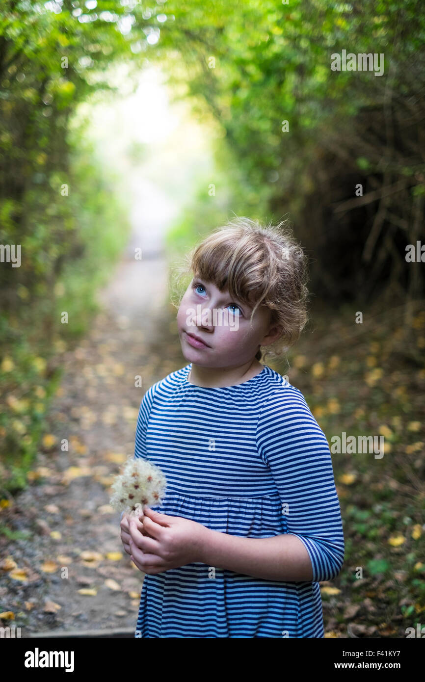 11 year old girl looking thoughtful in the woods - Stock Image