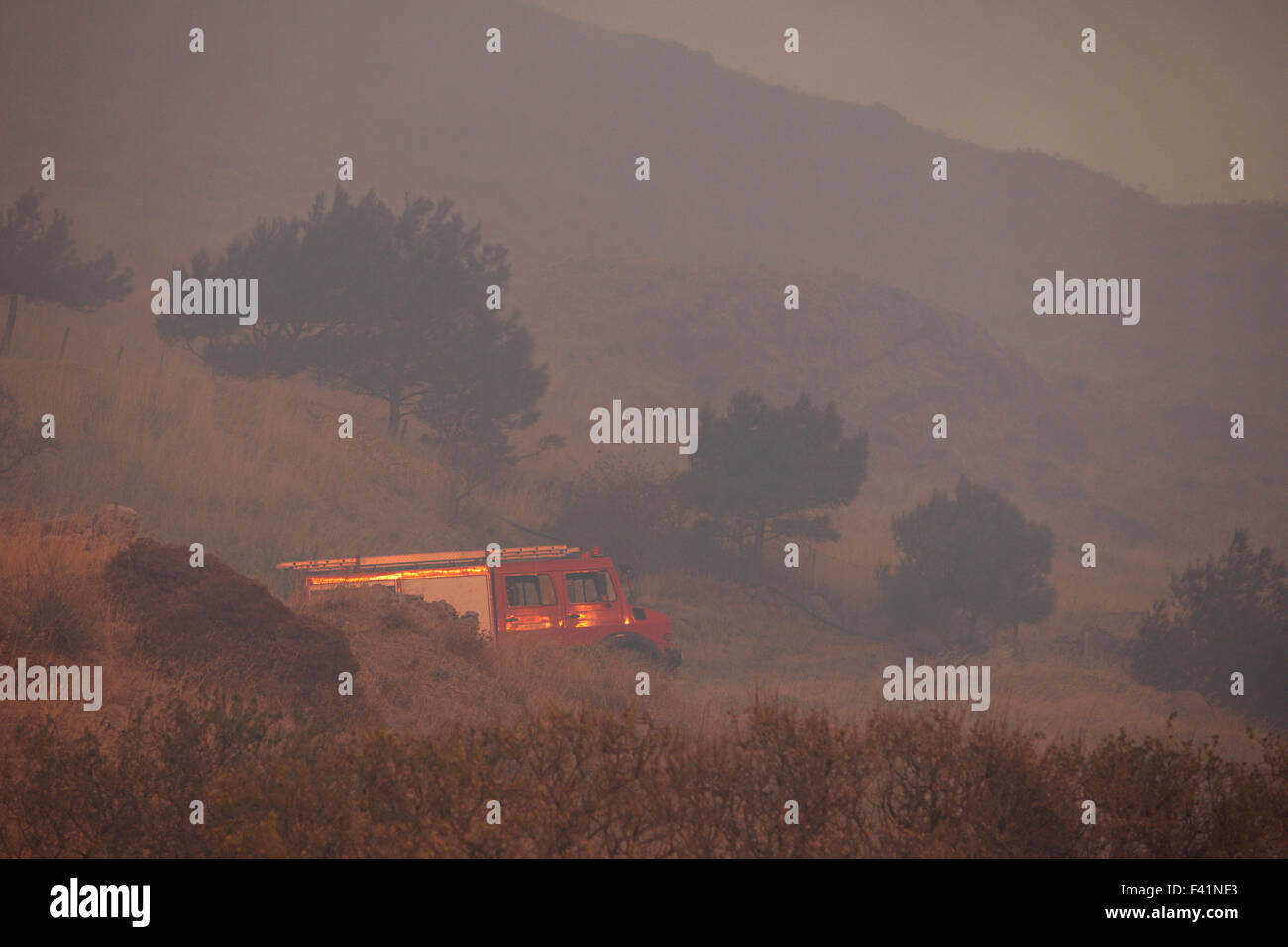 Greek fire brigade vehicle parked in the middle of a field during a live fire service summer operation in Greece. - Stock Image