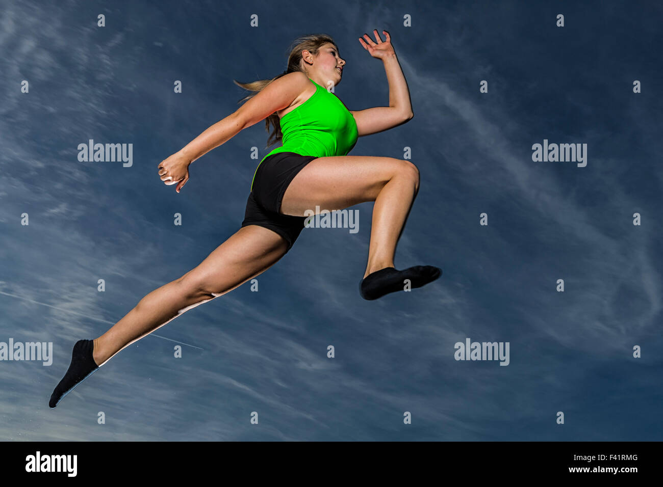 Young woman, 18 years old, leaping, against the evening sky - Stock Image
