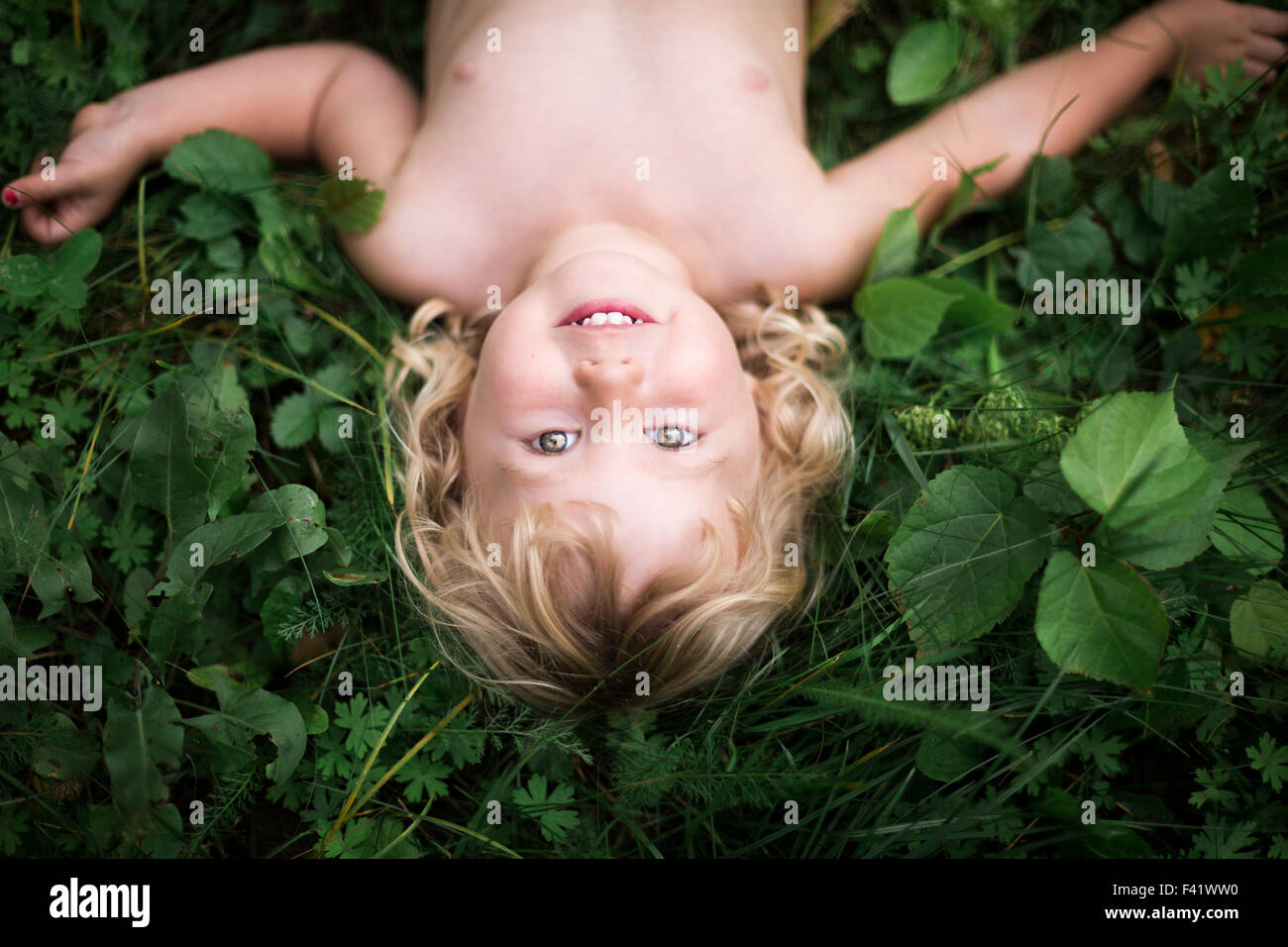 girl gazing skywards from the grass - Stock Image
