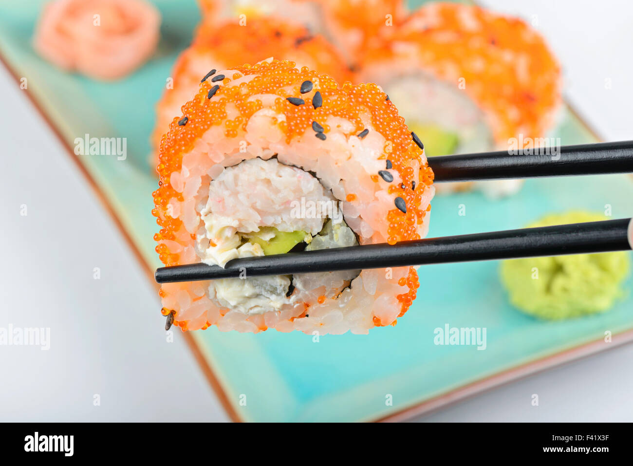 Sushi roll with black chopsticks - Stock Image