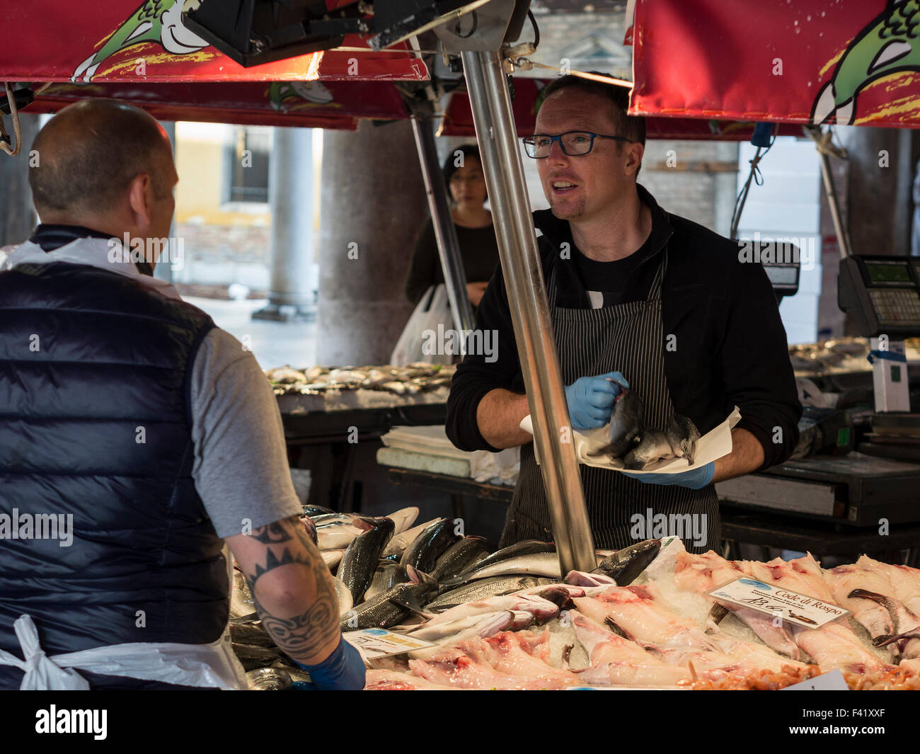 Customer and Fish Monger on Fish stall inside Rialto Market in Venice - Stock Image