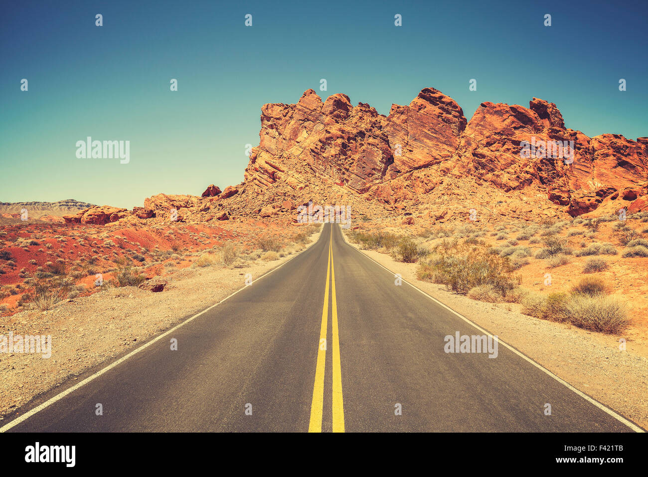 Retro stylized road through rocky desert in Valley of Fire State Park, Nevada. - Stock Image