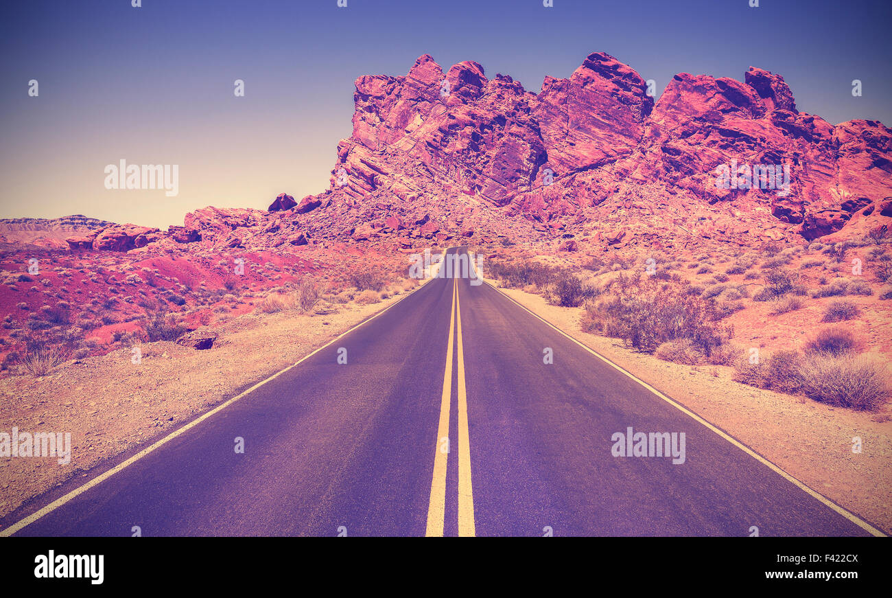 Vintage retro stylized road through rocky desert in Valley of Fire State Park, Nevada. - Stock Image