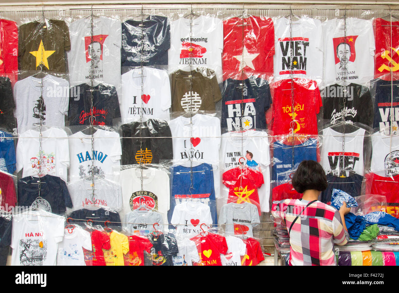t shirts for sale with vietnamese lady browsing at a store in Hanoi old quarter,Vietnam,Asia - Stock Image