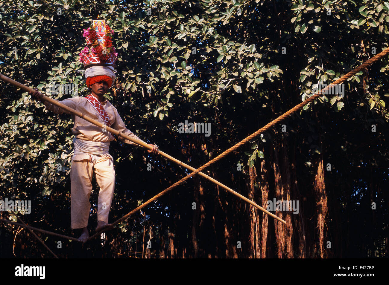Tightrope walker. He is carrying on his head the representation of a hindu deity ( India) - Stock Image