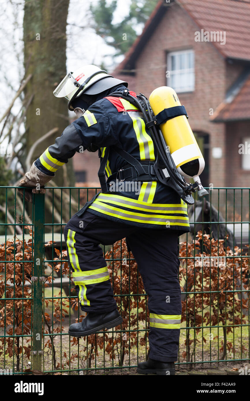 Fireman in action with oxygen bottle - Stock Image