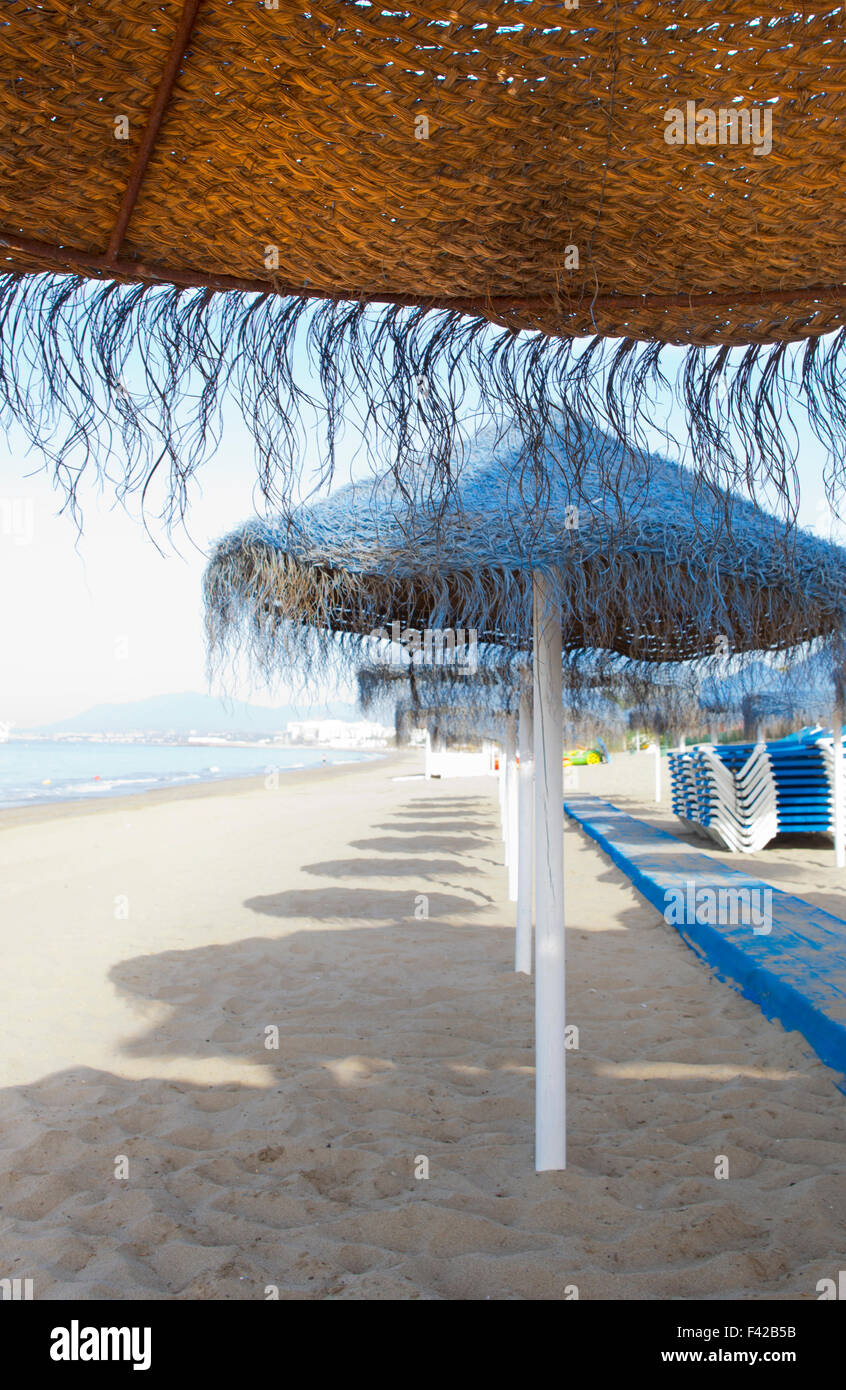 Rustic blue umbrellas made of natural fibers on a nice beach in Costa del Sol Spain - Stock Image