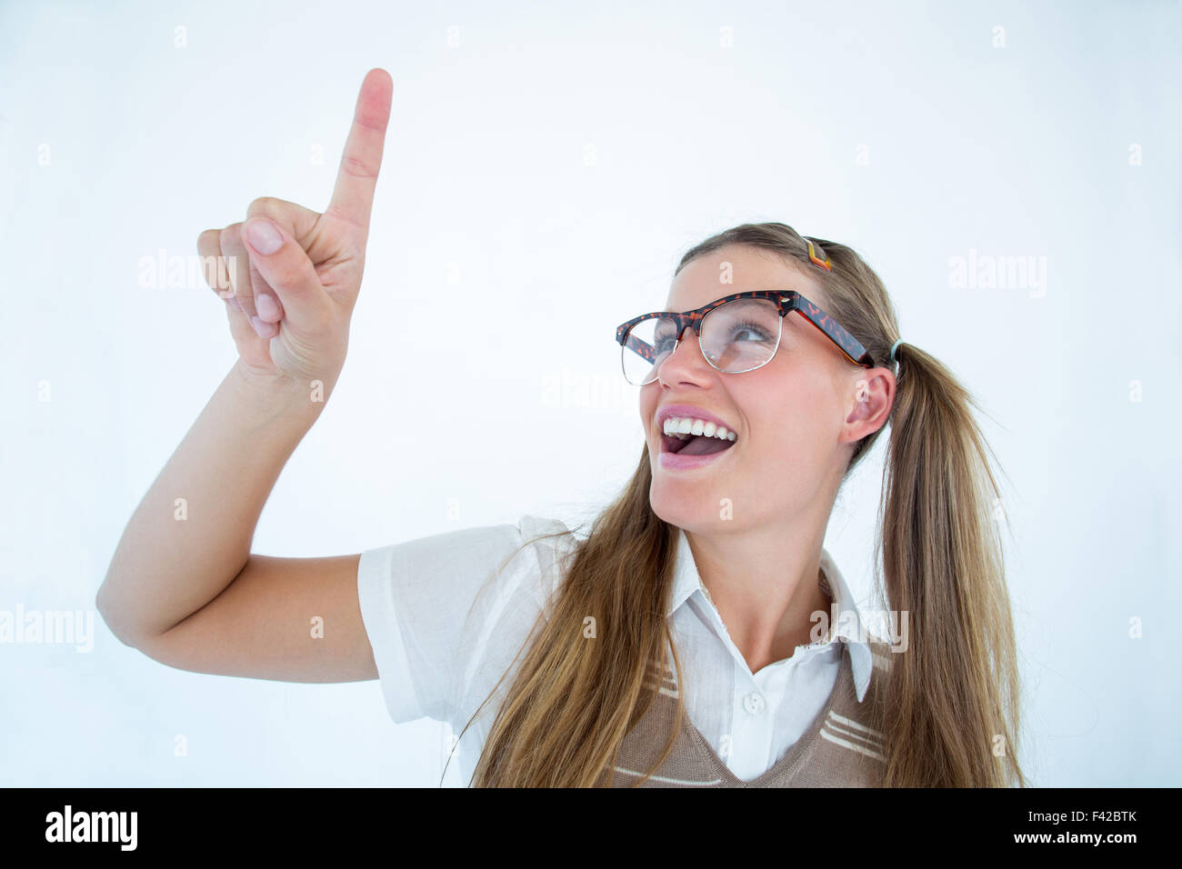 Happy geeky hipster pointing - Stock Image