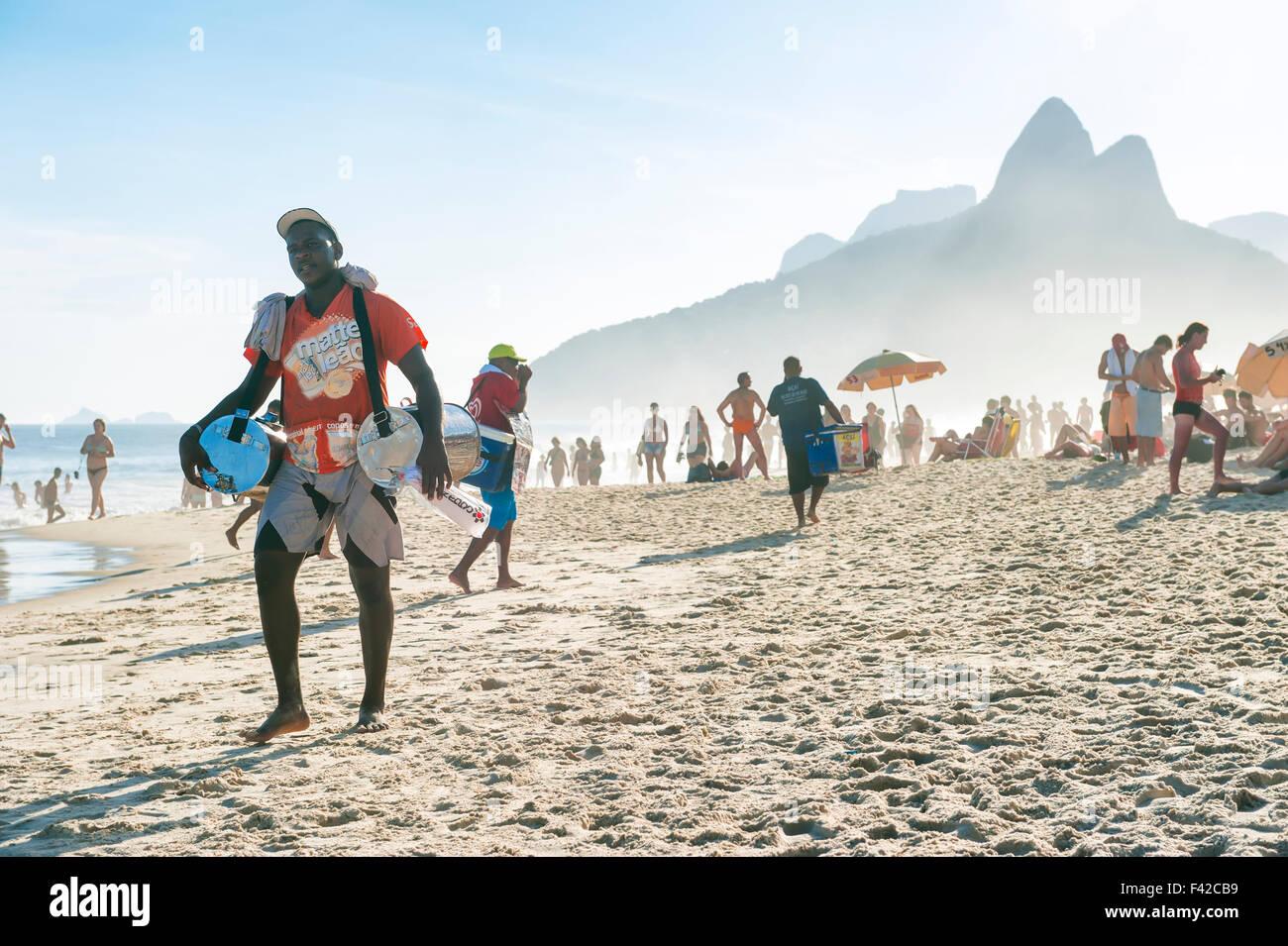 RIO DE JANEIRO, BRAZIL - JANUARY 20, 2013: Vendor selling Brazilian mate iced tea walks on Ipanema Beach on a misty - Stock Image