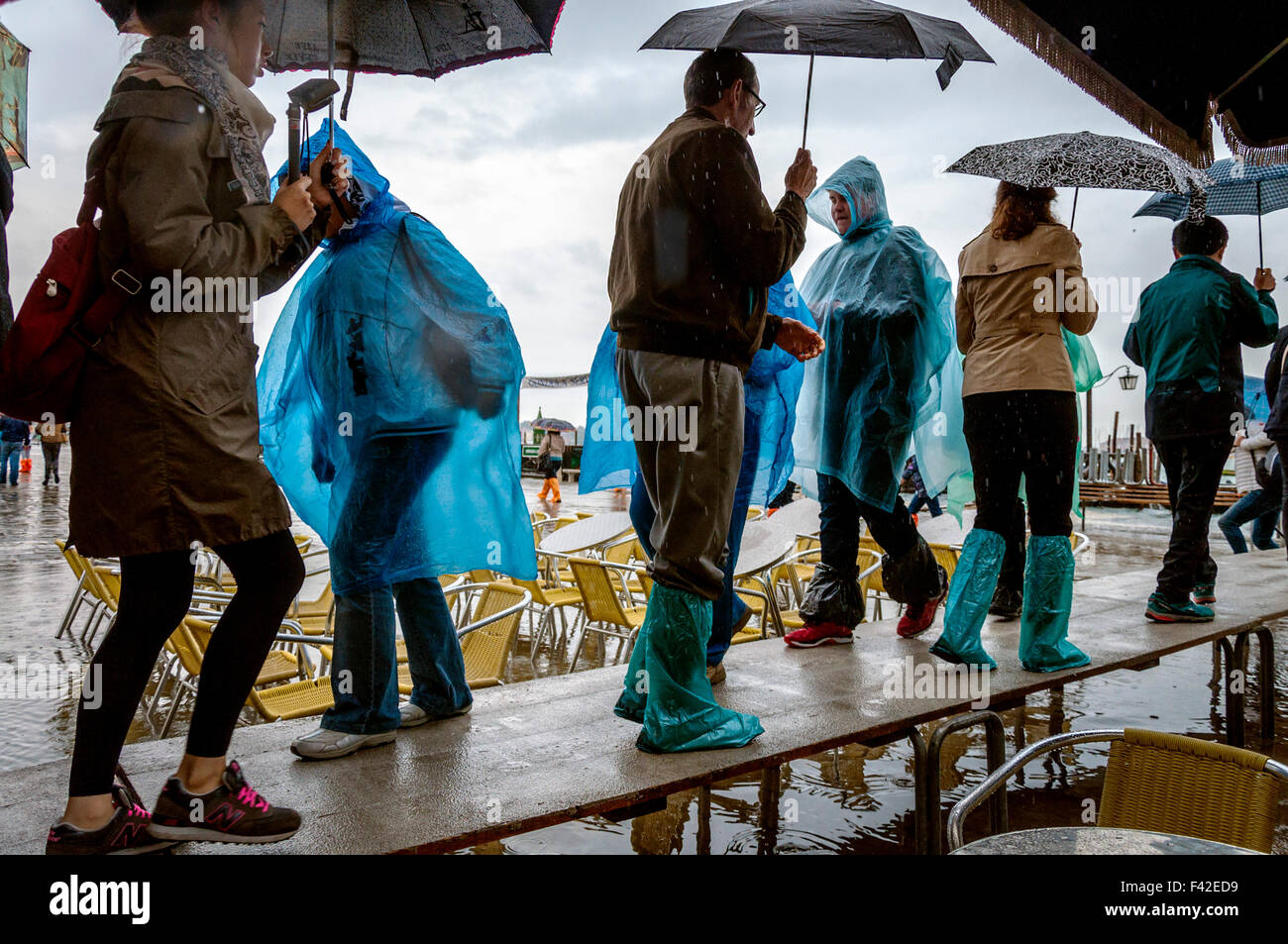 St Marks Square, Venice, Italy. 14th October 2015. People in Piazza San Marco wearing rain ponchos and galoshes - Stock Image